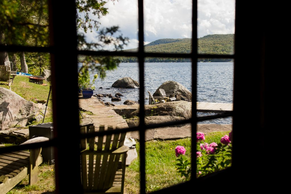 The view of an adirondack lake wedding site through the windows of a boathouse