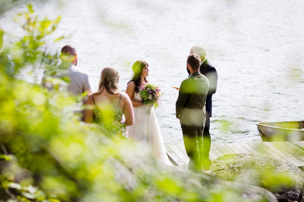 A view through the trees of a bride and groom and a couple guests standing by a lake during a wedding ceremony