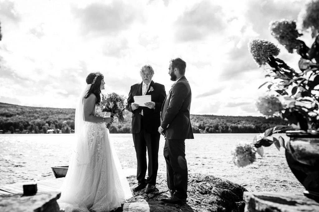 A bride and groom get married on a rock near a lake