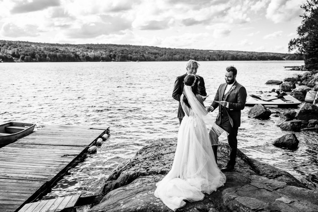 A bride and groom stand on a rock next to a lake during their wedding ceremony