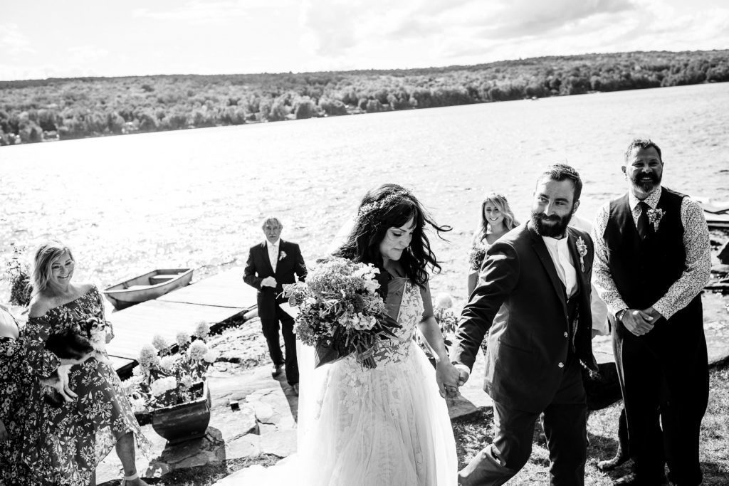 A black and white photo of a bride and groom leaving their lakeside wedding ceremony