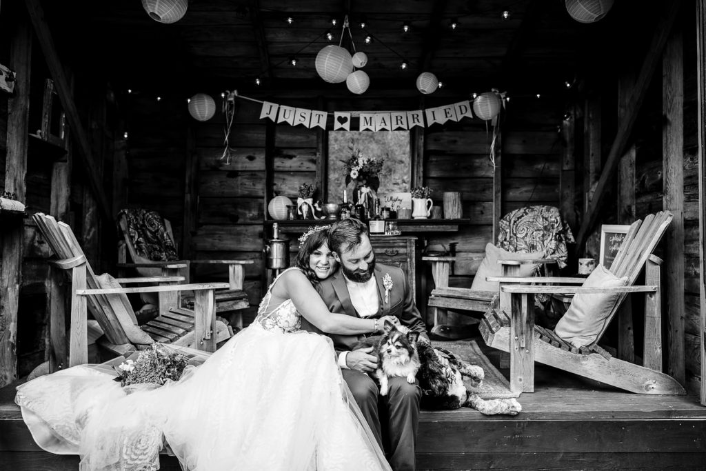 A bride smiles and hugs her groom as he pets their dogs beneath a just married sign