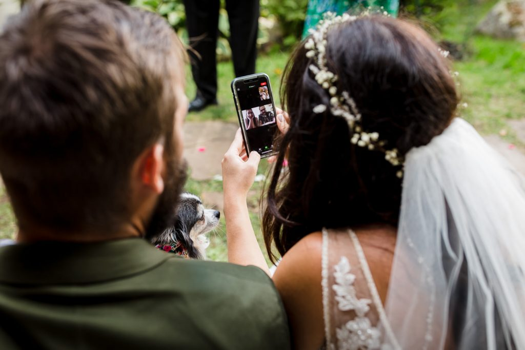 A bride and groom check in with wedding guests via zoom at their covid wedding