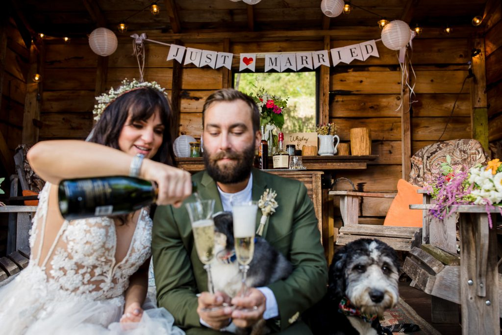 A bride and groom pour champagne in front of a just married sign at their adirondacks lake wedding