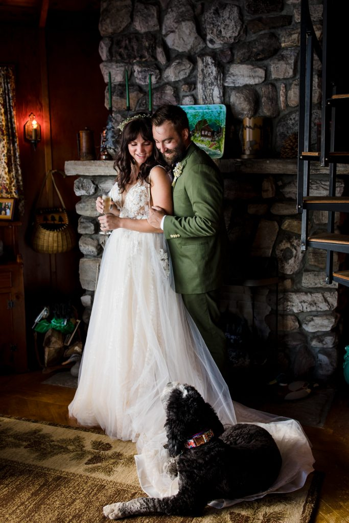A bride and groom in front of a stone fireplace with their dog curled up on the train of the wedding gown