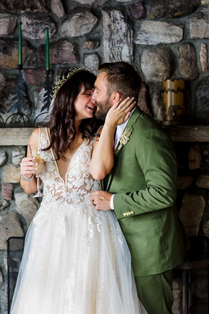 A bride and groom kiss in front of a stone fireplace