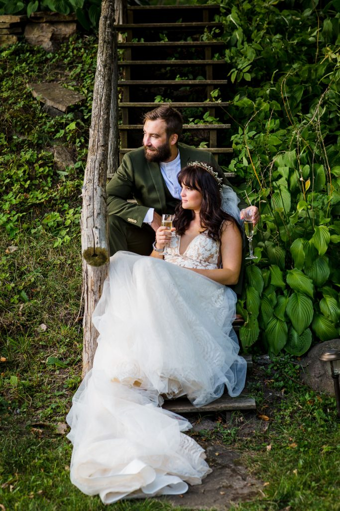 A bride and groom sit on wood stairs holding champagne glasses amongst greenery