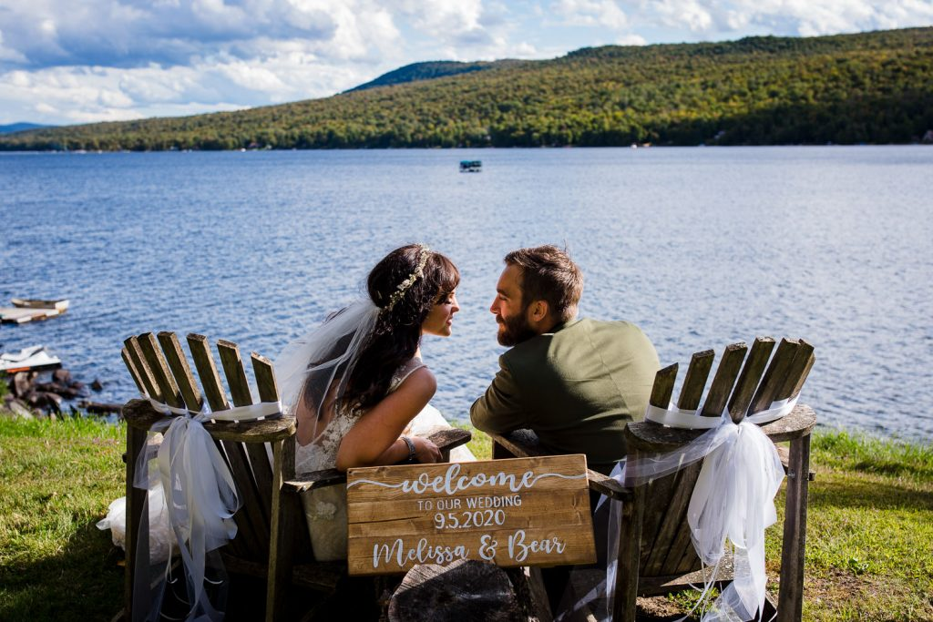 A bride and groom sit in adirondack chairs above a lake during their adirondacks lake wedding