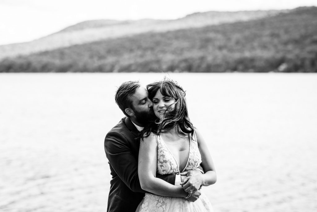 A black and white photo of a groom embracing a bride above a lake and mountains in the adirondacks