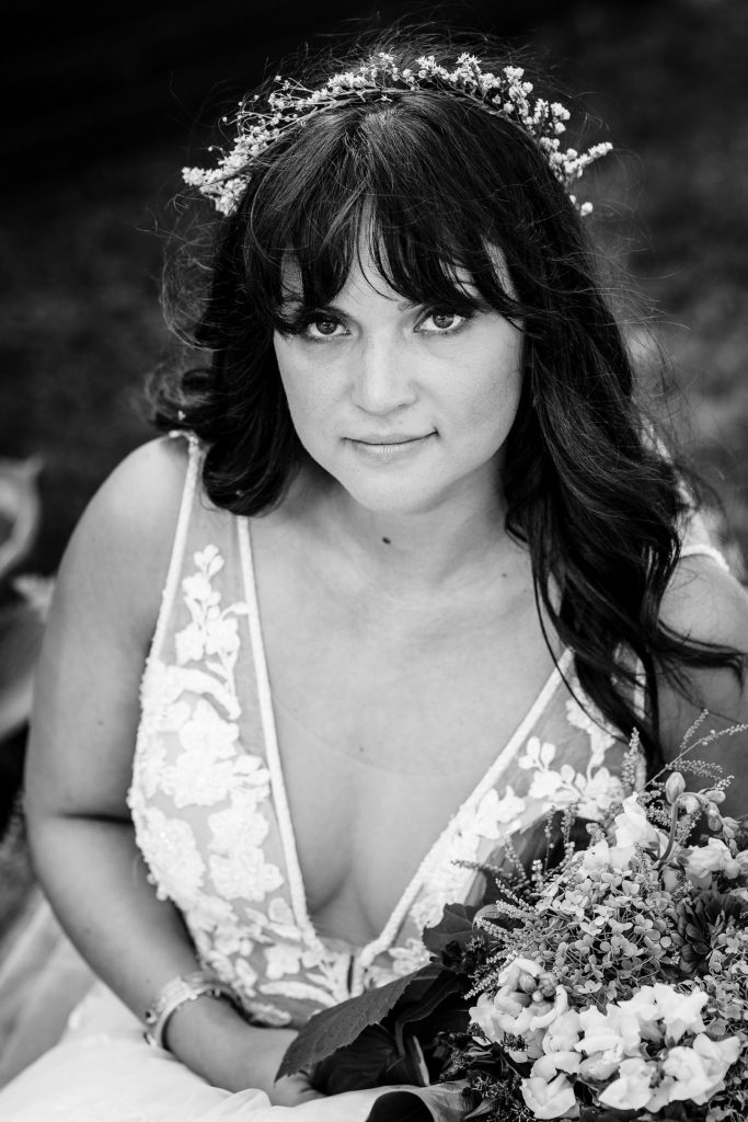 A black and white photo of a bride wearing a flower crown