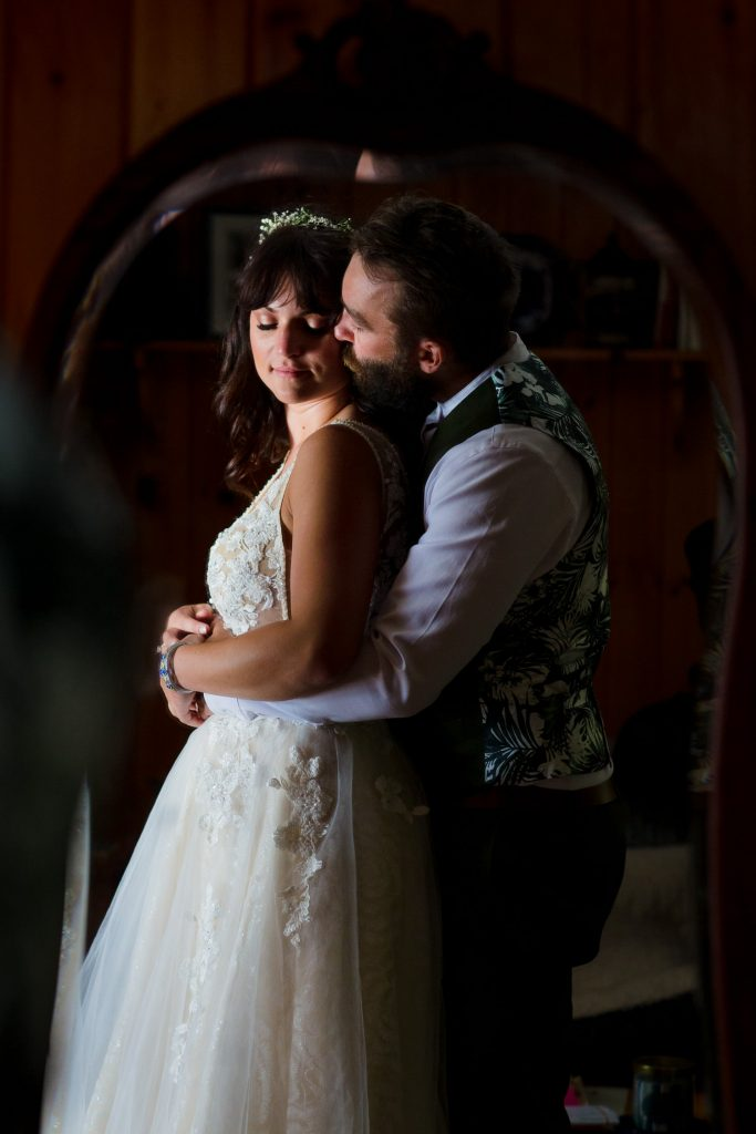 A reflection in an antique mirror of a bride and groom cuddling