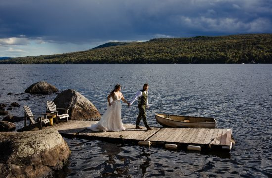 A bride and groom walk a dock hand in hand at an adirondacks lake wedding