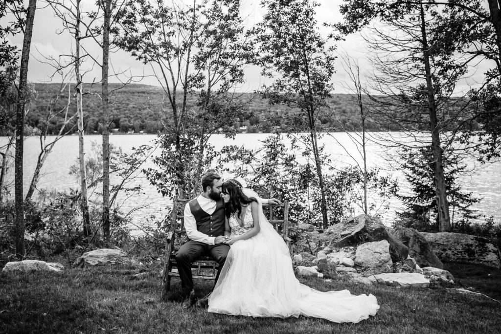 A black and white photo of a bride and groom sitting on a bench in the woods by a lake