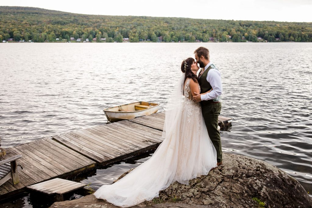 Bride and groom embrace on a boulder along chateaugay lake