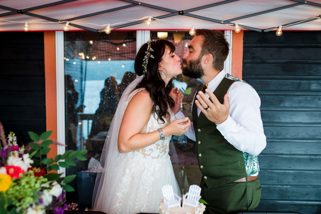 Bride and groom kiss after exchanging bites of wedding cake