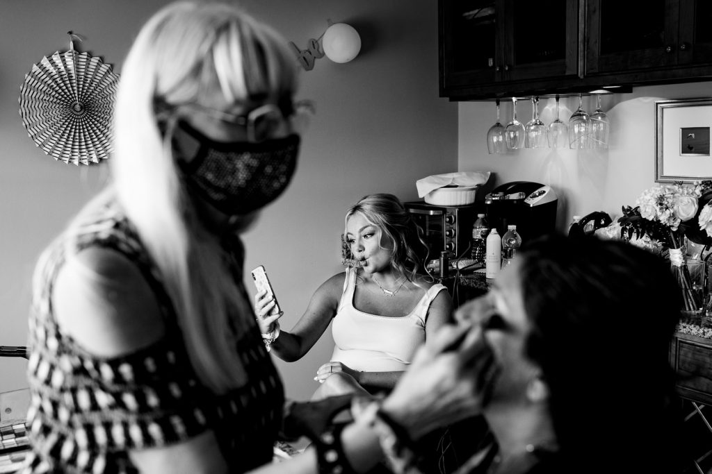 A woman is getting her makeup done as a girl in the background poses for a selfie