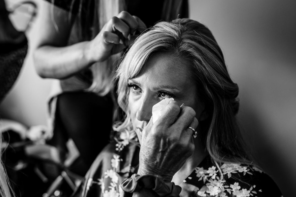 A hand dabs tears from a brides eyes as she gets her hair done