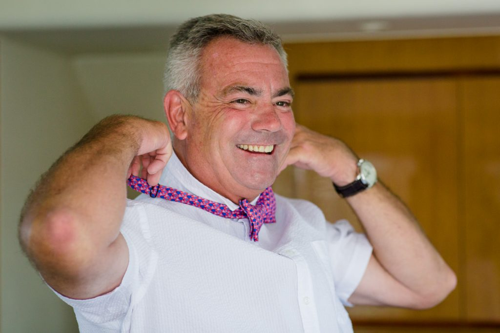 A groom puts on his pink bowtie to get ready for the wedding