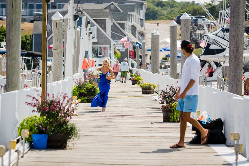 A bridesmaid in a blue dress walks down the dock at Champlin's marina to her parents block island wedding
