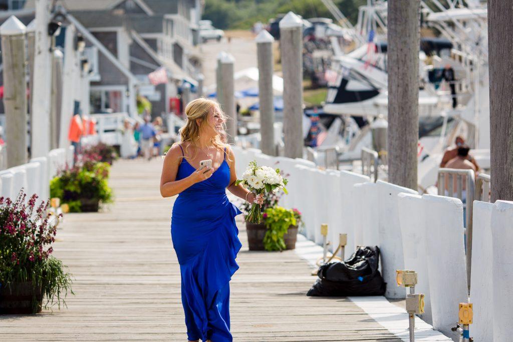 A woman in blue walks down a dock