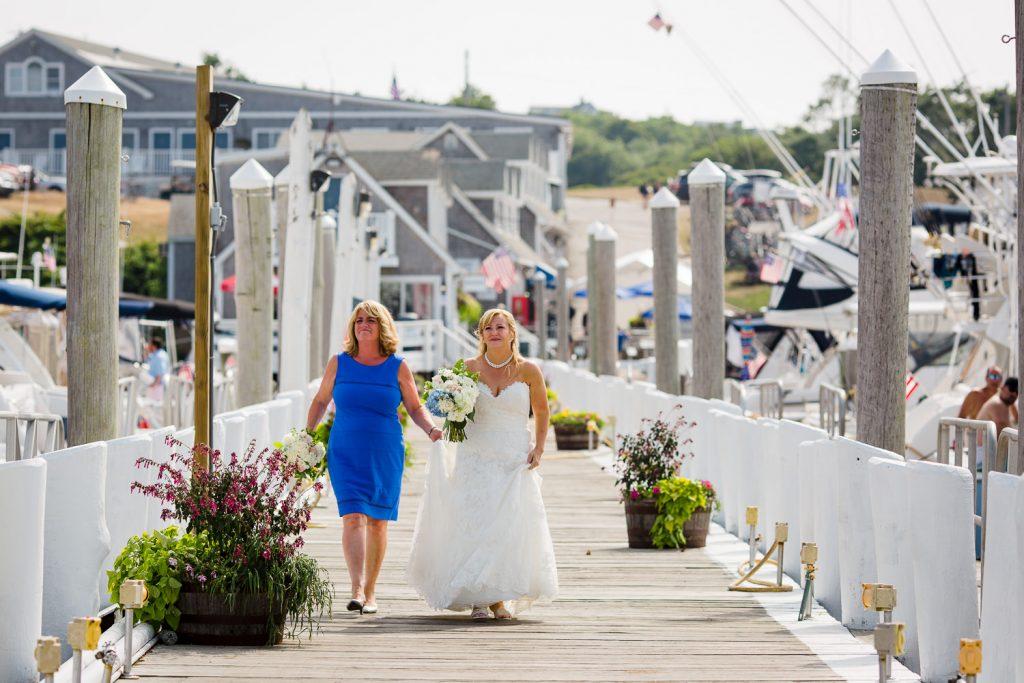 A bride and her bridesmaid walk down the dock at Champlin's Marina in block island