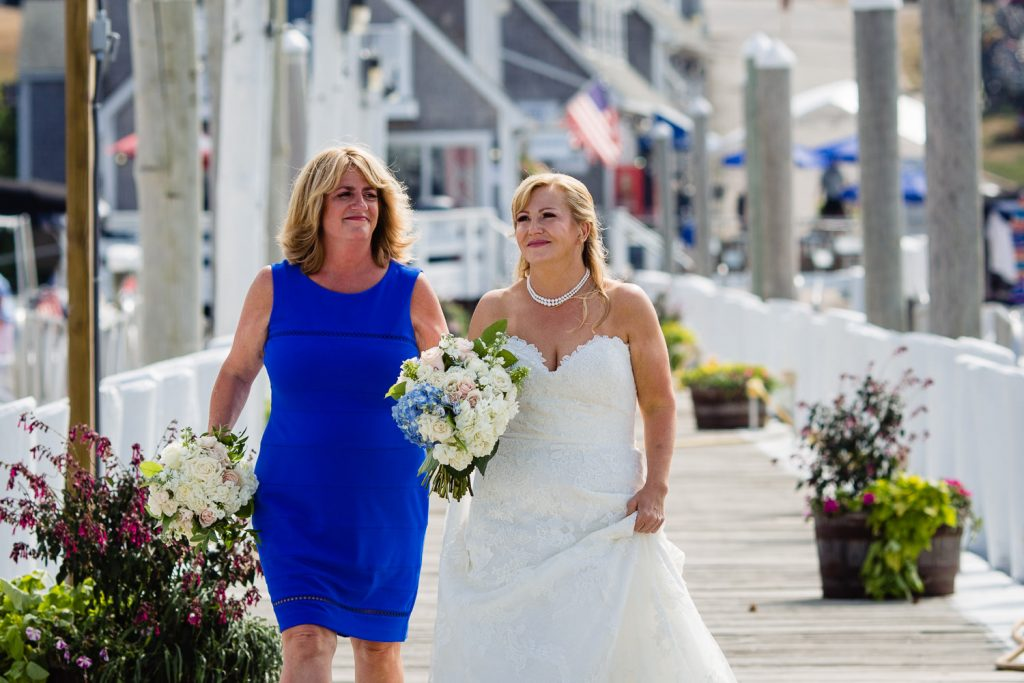 A woman in blue helps a bride walk down a dock to her wedding