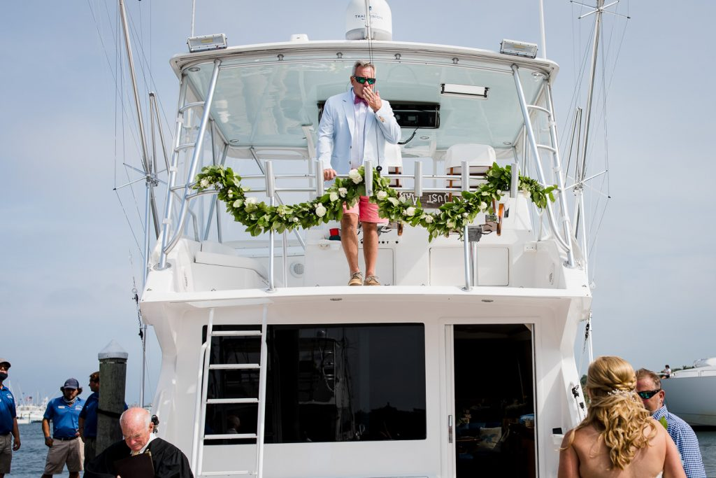 A man stands up on the bride of a boat and blows a kiss to his bride below