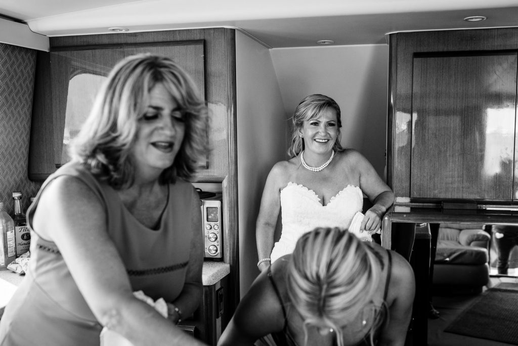 The bride smiles as her sister and daughter get ready for the wedding