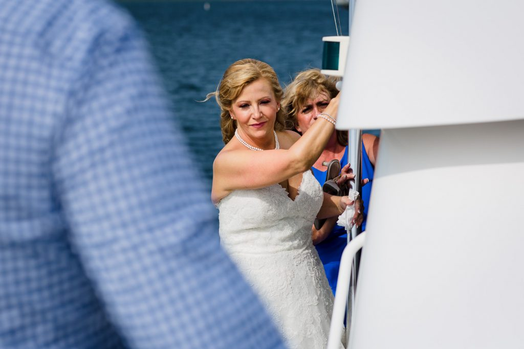 A bride hangs off the side of the boat as she processes to her wedding ceremony