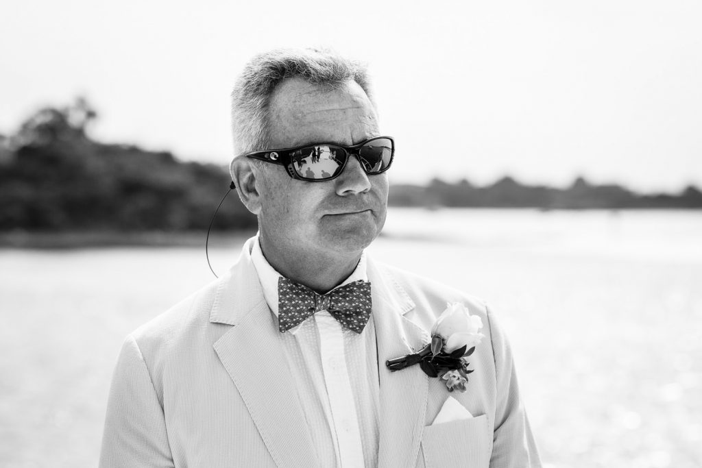 A groom in sunglasses looks on as his bride walks towards him for their wedding ceremony