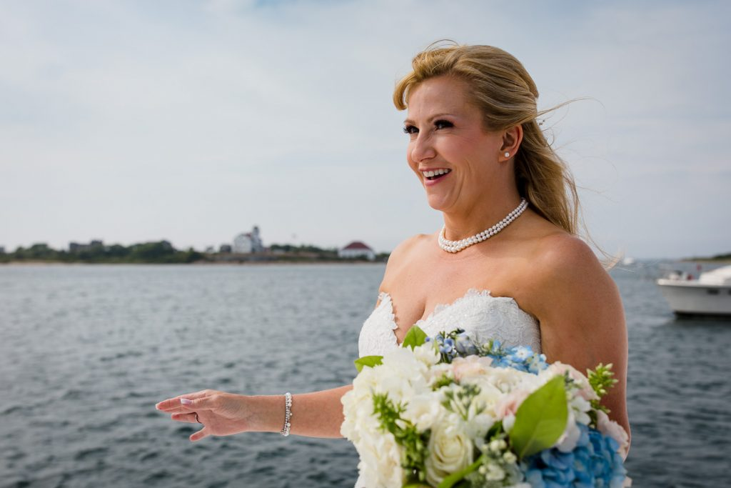A bride smiles as she reaches the front of the boat for her block island wedding