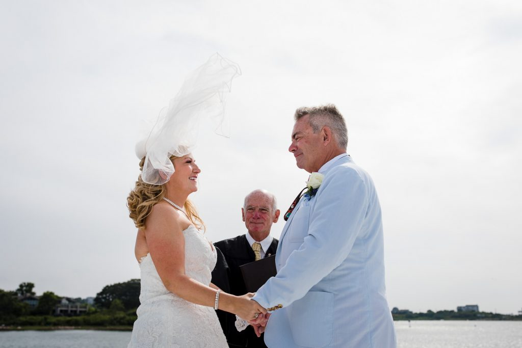 A brides veil flies up in the air during her wedding ceremony