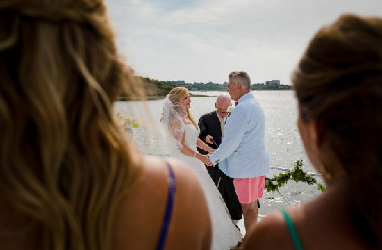Two guests watch as the bride and groom get married on the bow of their boat during their block island wedding