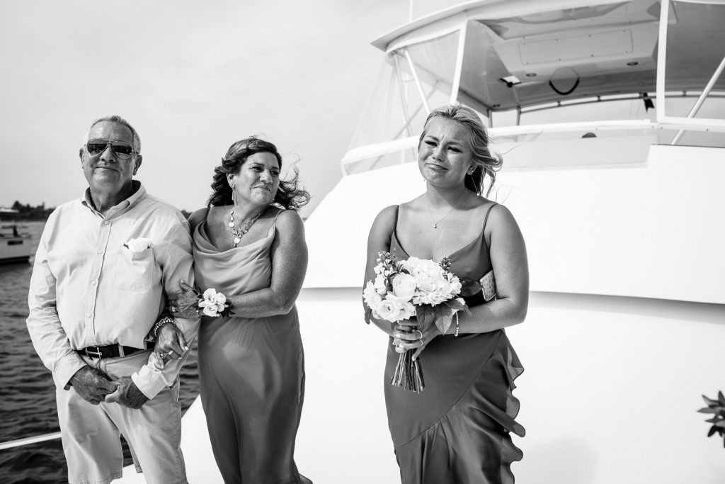 Two guests smile and look at the daughter of the groom as she tears up during the boat wedding ceremony
