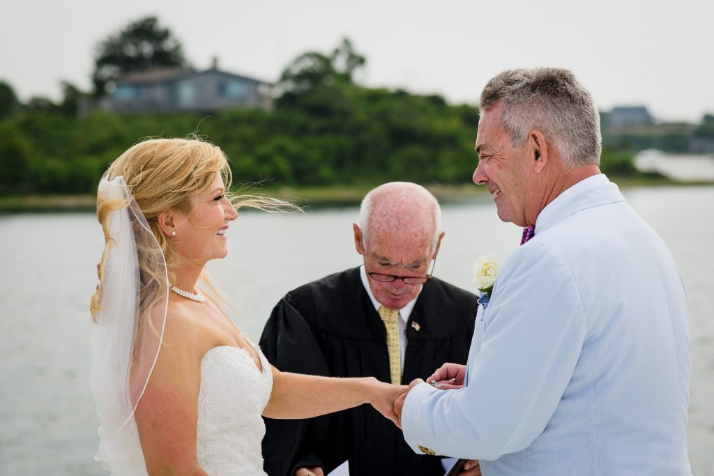 A groom slides the ring on the brides finger at their boat wedding