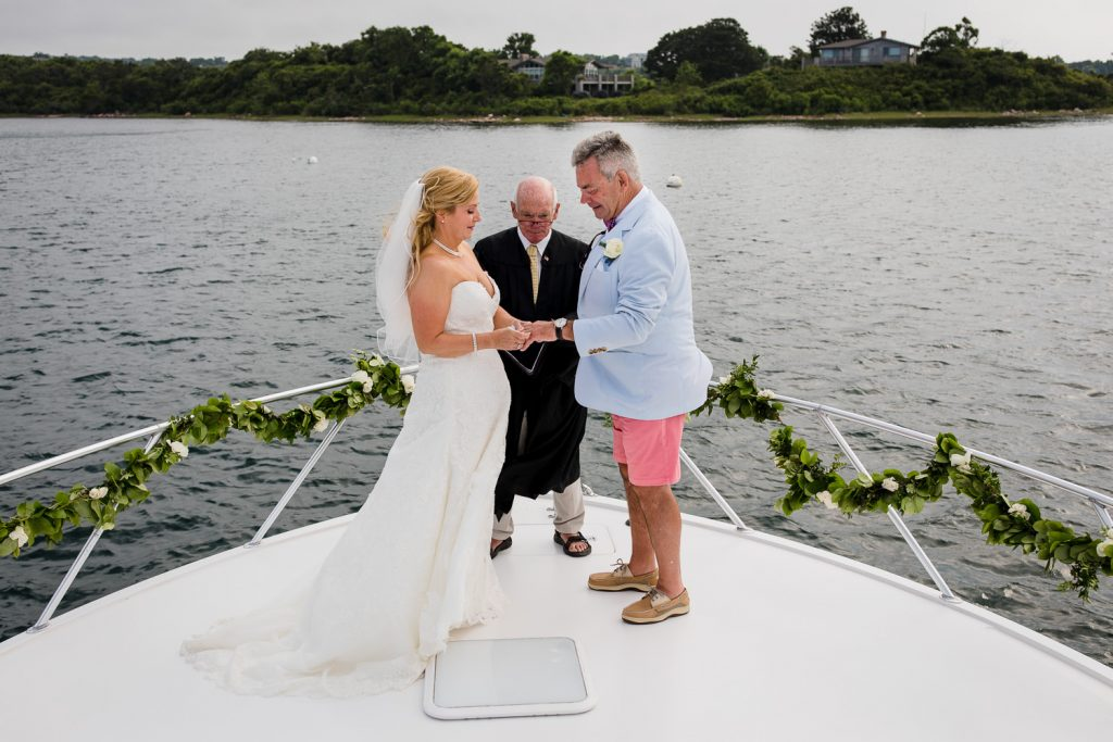 A bride and groom and officiant standing on the bow of a boat doing a wedding ceremony in block island