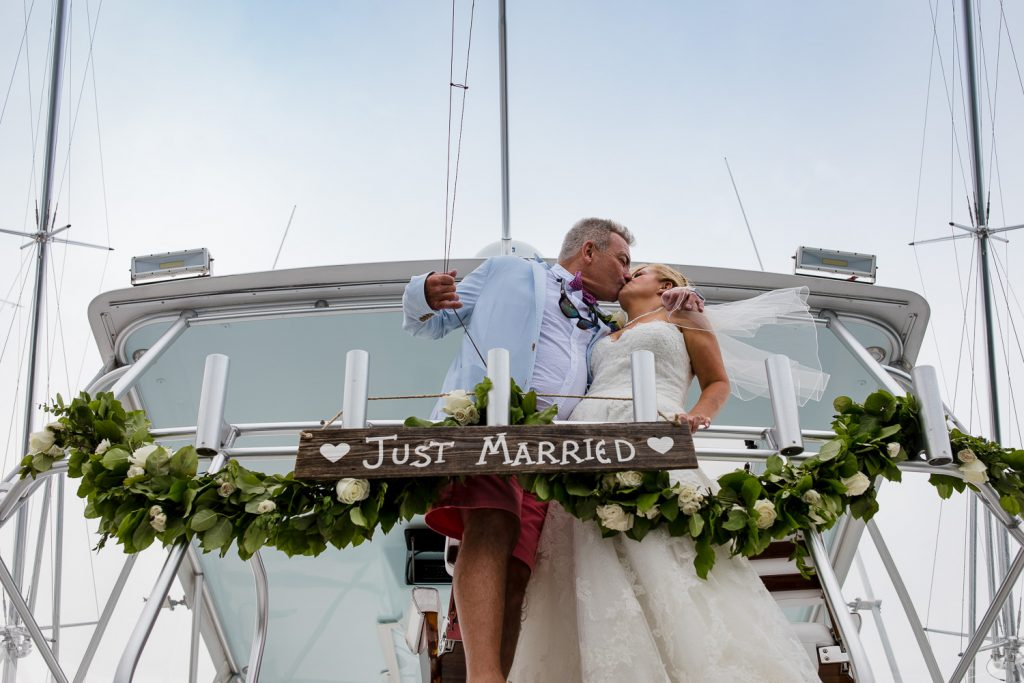 A bride and groom kiss on the bridge of a boat with flowers and a just married sign