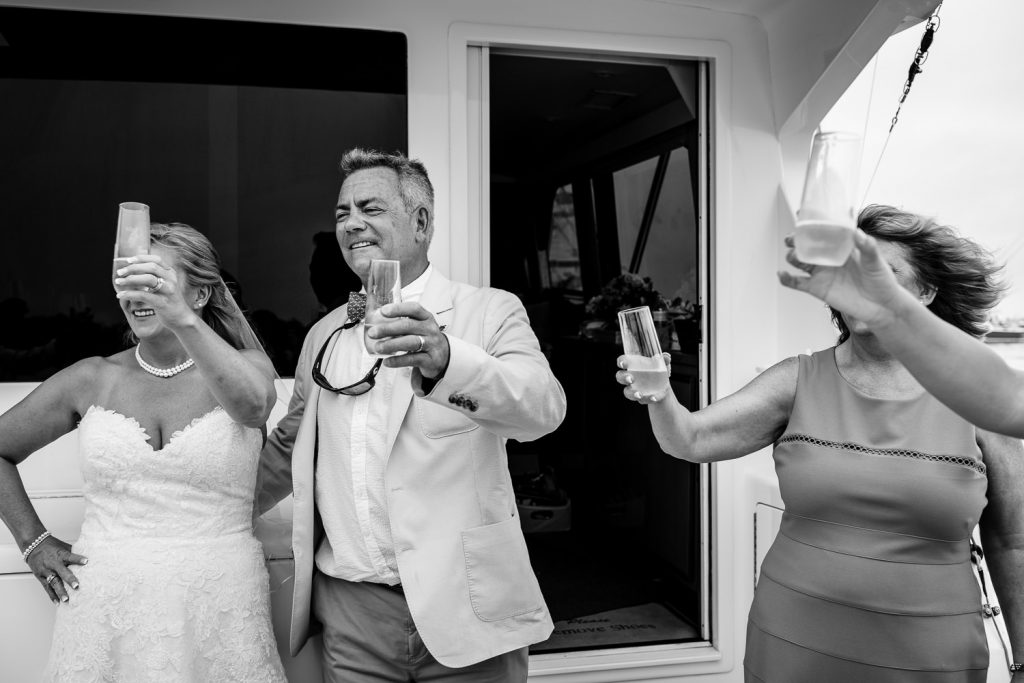 A bride and groom and others raise their champagne glasses to toast at their boat wedding