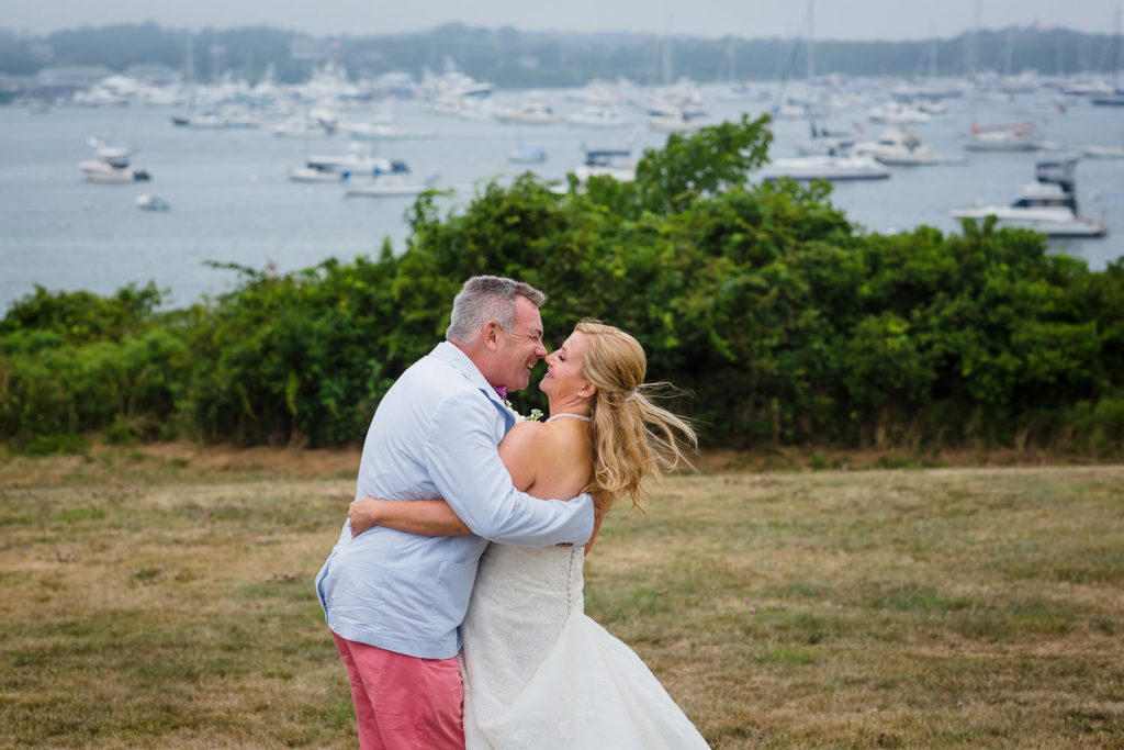 A groom dips his bride on the lawn at Sullivan House at their block island wedding with boats in the background