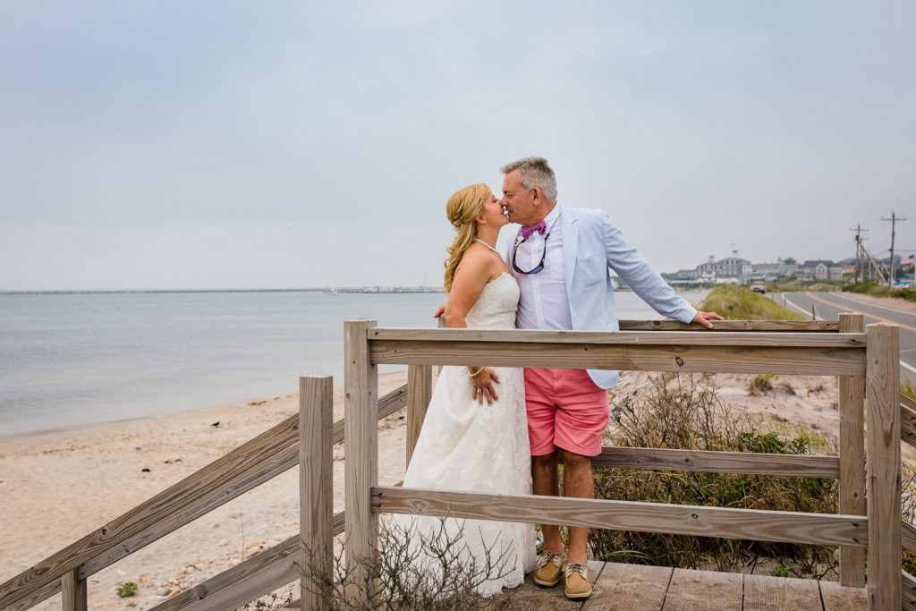 A bride and groom stand on the stairway to crescent beach for photos after their block island wedding