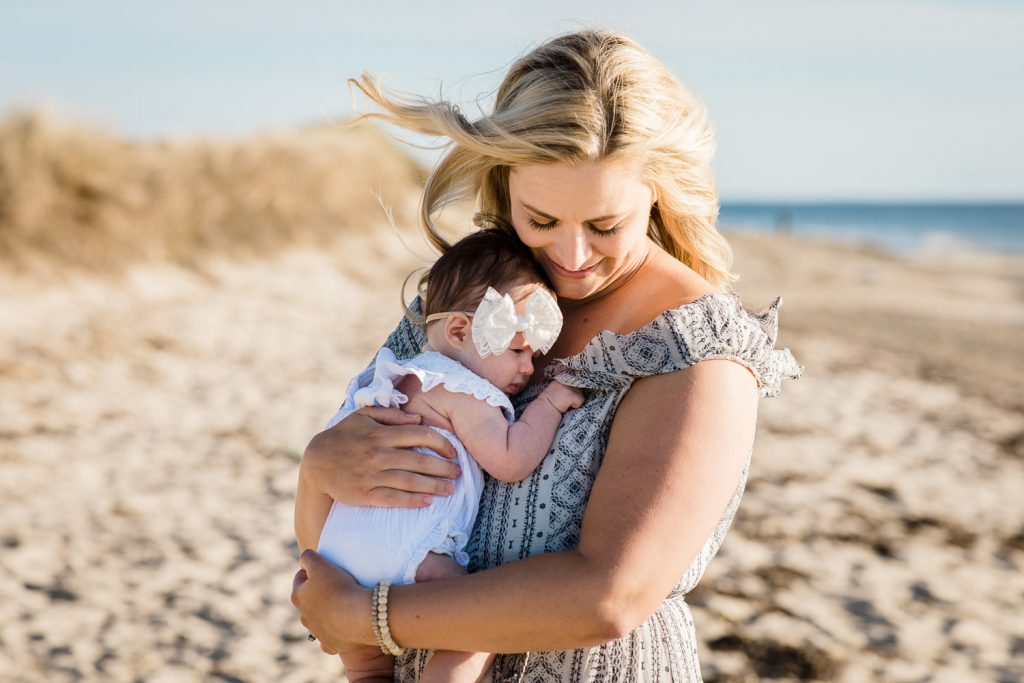A woman holds her baby girl to her chest as her hair blows in the wind at a cape cod family photography session