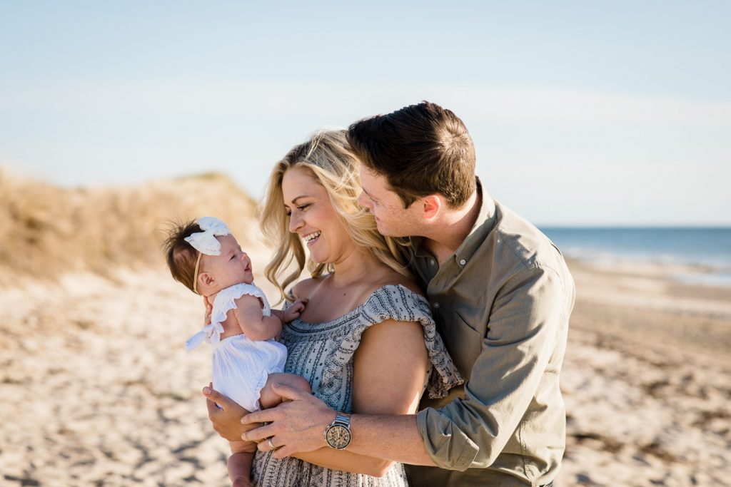 A man and woman embrace and look at their infant daughter