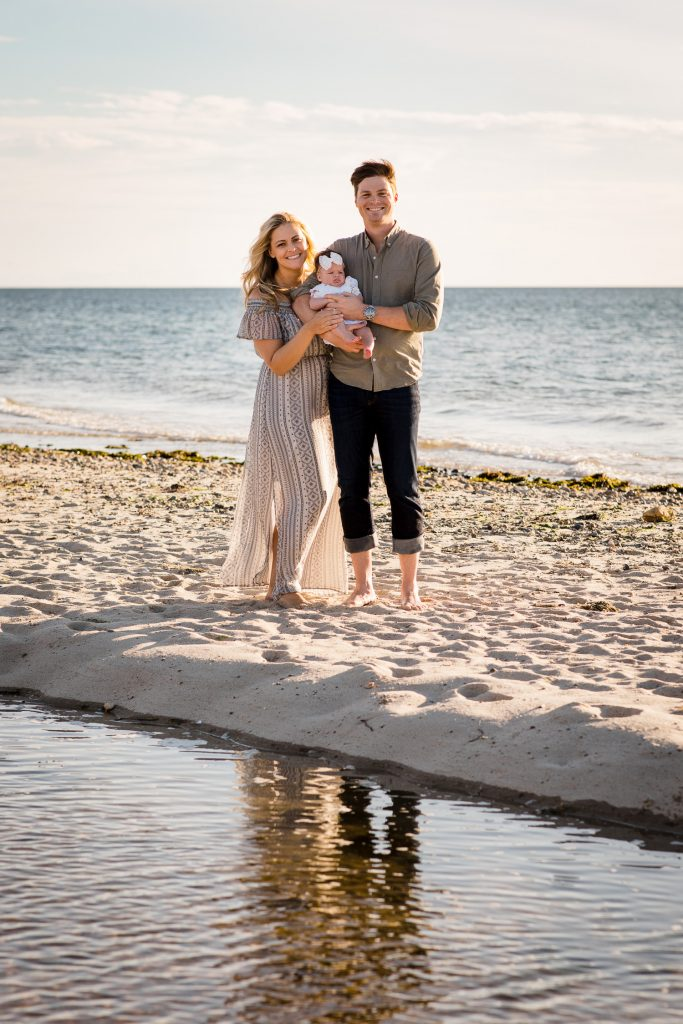 A man and woman stand on a sandy beach with their baby the ocean behind them and a reflecting pool in front of them