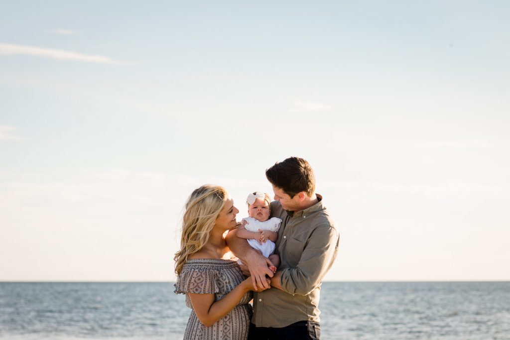 A man and woman hold their baby between them with the ocean behind them