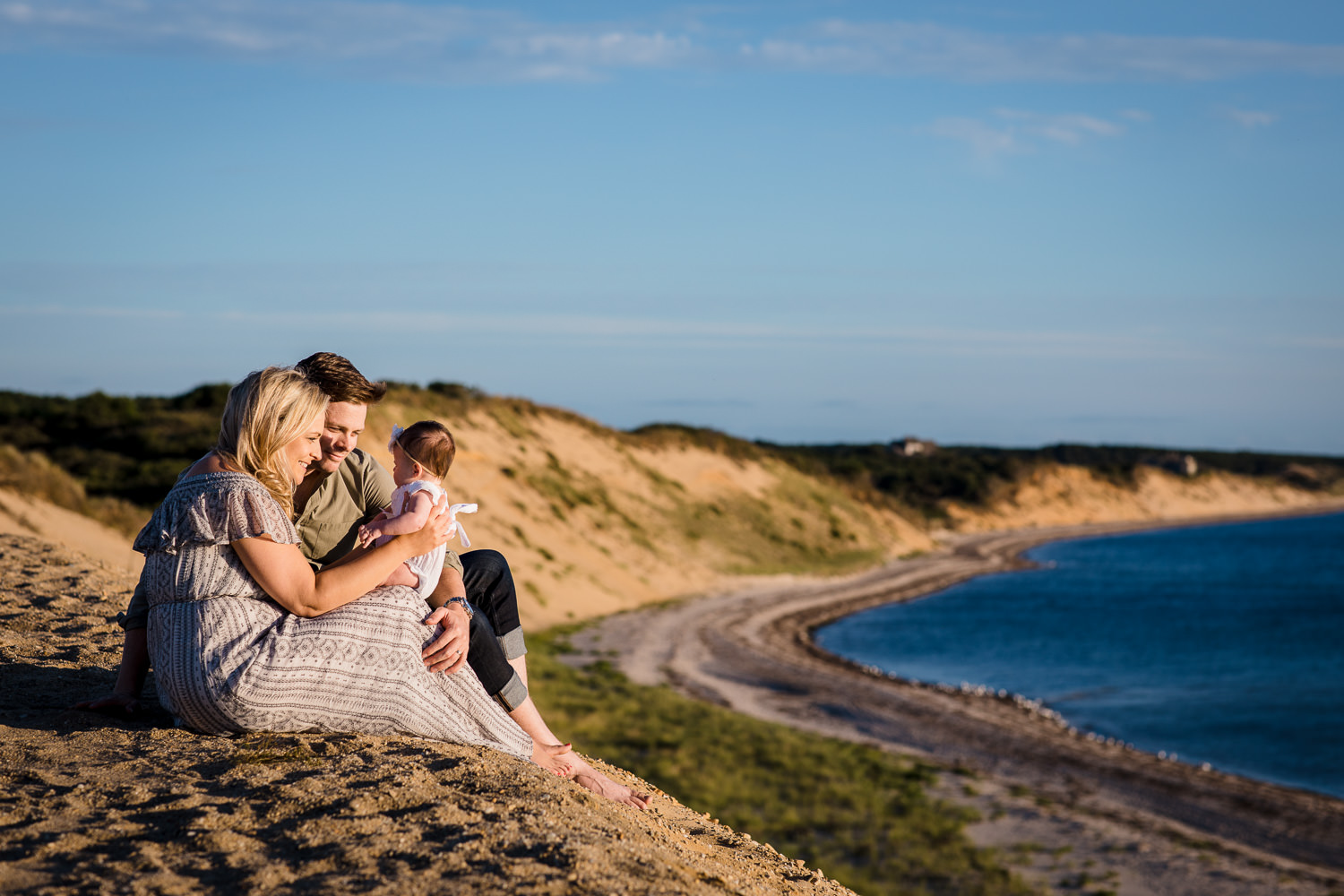 A man and woman sit at the edge of a large sand dune holding their baby girl