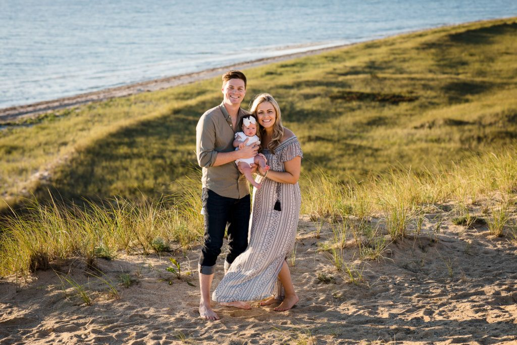 A man and woman hold their infant baby on a bluff overlooking the ocean