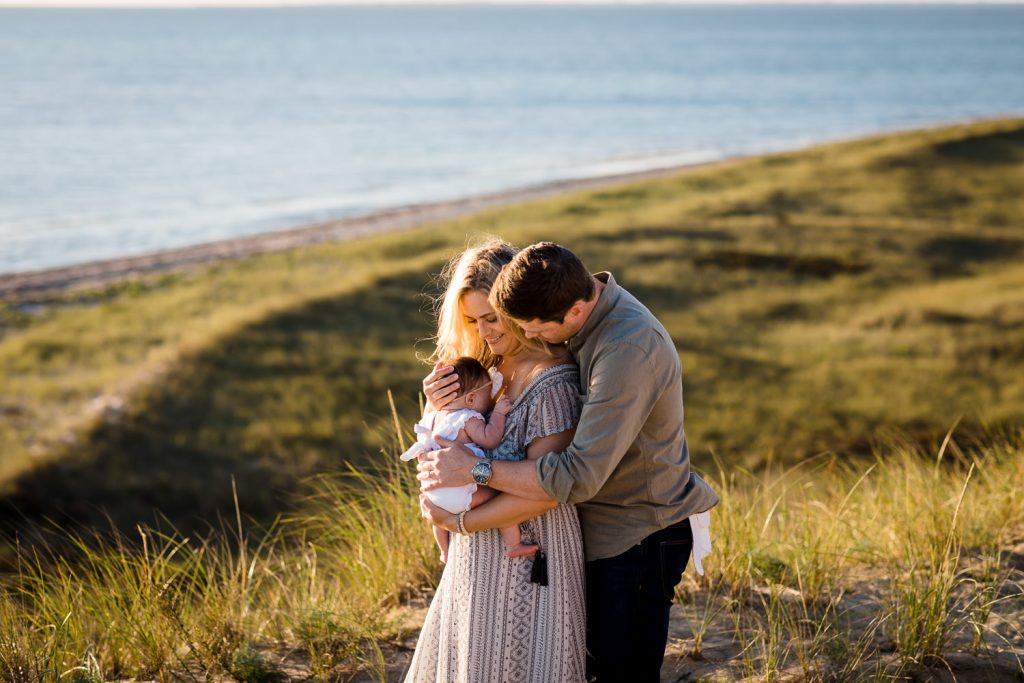 A man and woman embrace their newborn on a bluff above the ocean