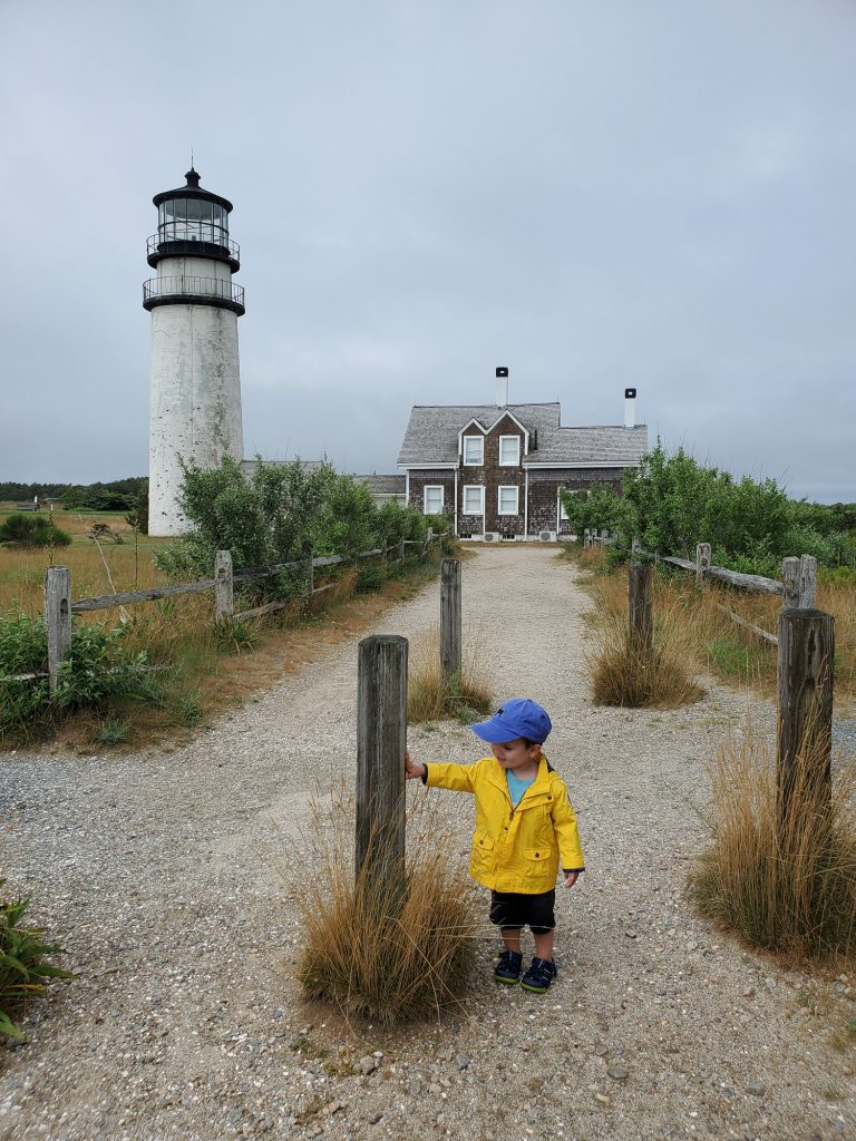 A little boy in a yellow rainjacket stands in front of highland lighthouse on cape cod