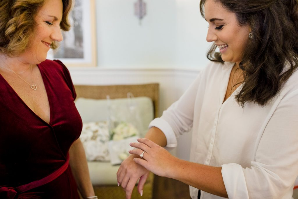 A bride and her mother smile as she puts on her bracelet
