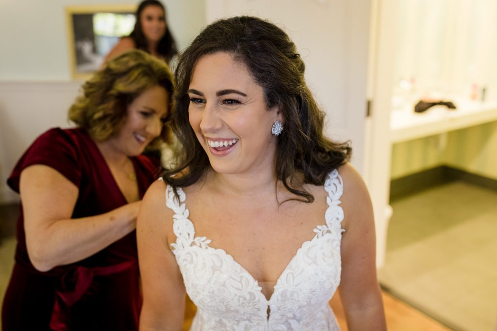 A bride laughs while getting ready